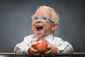 Cheerful baby on a gray background with a white shirt eating an apple
