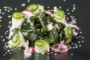 Fresh healthy wakame seaweed salad with cucumber and radish
